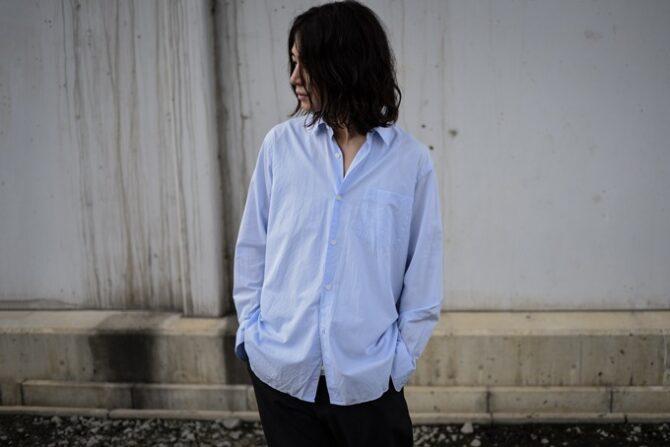 コモリシャツを着て、パンツのポケットに手を入れる男性