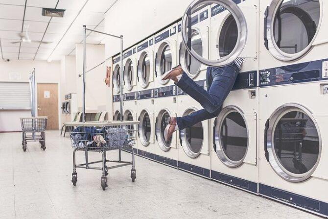 洗濯機に顔を突っ込む男性