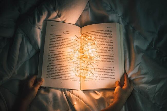 暗い部屋で開いた本の上に明かりが点っている