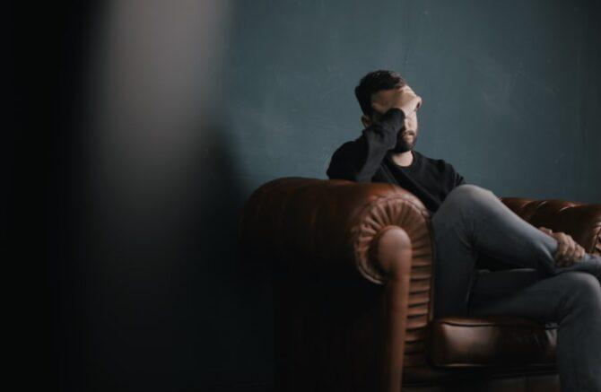 ソファに座って頭を抱える男性