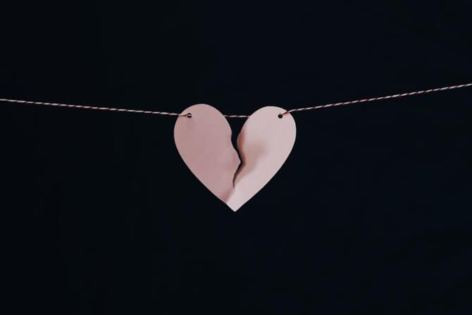 紐に吊られて破れかけているハート型の紙