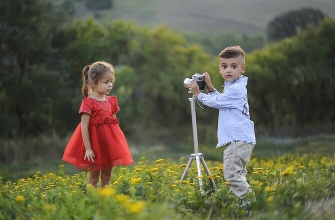 花畑で女の子の写真を撮る男の子
