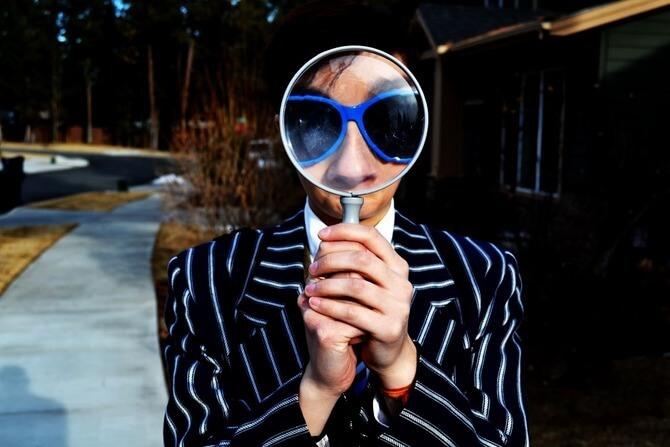 虫眼鏡を覗き込む男性