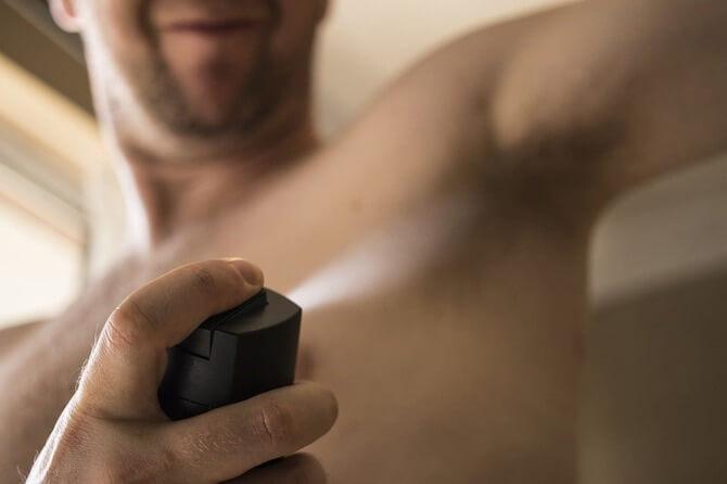 腋に制汗スプレーをする男性